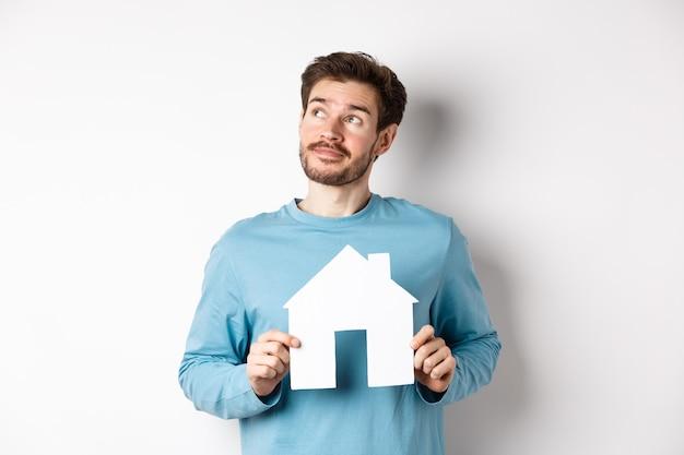 Concept immobilier et assurance. homme rêvant d'acheter une propriété, tenant une découpe de maison en papier et regardant le coin supérieur gauche, imagerie de choses, fond blanc.