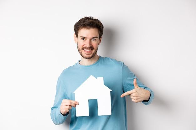 Concept immobilier et assurance. souriant jeune homme pointant sur la découpe de maison de papier et à la recherche de plaisir, acheter un appartement, debout sur fond blanc.
