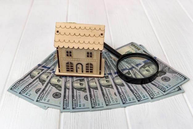 Concept immobilier avec des dollars et modèle de maison en bois