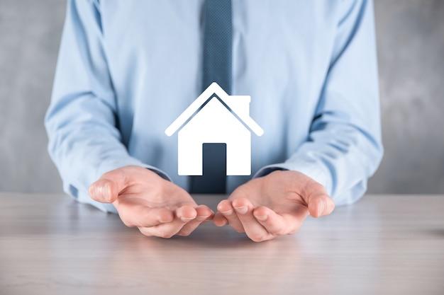 Concept immobilier, homme d'affaires détenant une icône de maison
