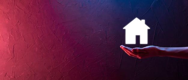Concept immobilier, homme d'affaires tenant une icône de la maison. maison en main. concept d'assurance et de sécurité de propriété. geste protecteur de l'homme et symbole de la maison