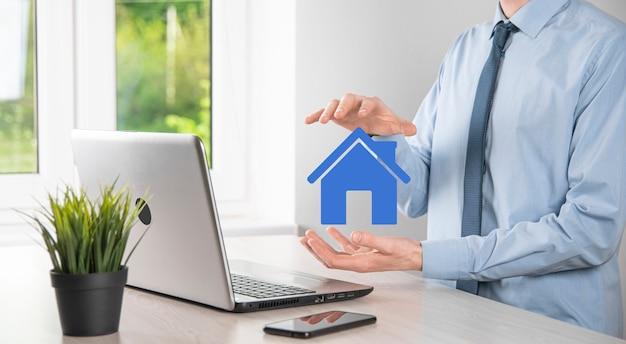 Concept immobilier, homme d'affaires tenant une icône de la maison. maison en main. concept d'assurance et de sécurité de propriété. geste protecteur de l'homme et symbole de la maison.
