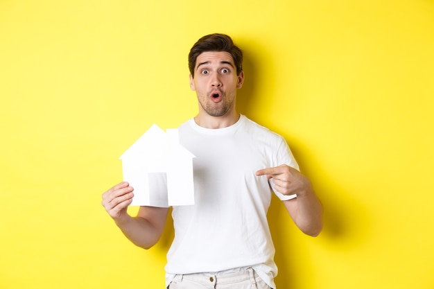 Concept immobilier. homme excité pointant le doigt sur le modèle de maison en papier, à la recherche de plat, debout sur fond jaune.