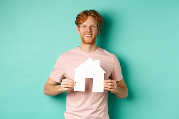 Concept immobilier. jeune homme aux cheveux rouges, vêtu d'un t-shirt, montrant la découpe de maison en papier et souriant heureux, debout sur fond de menthe. copier l'espace