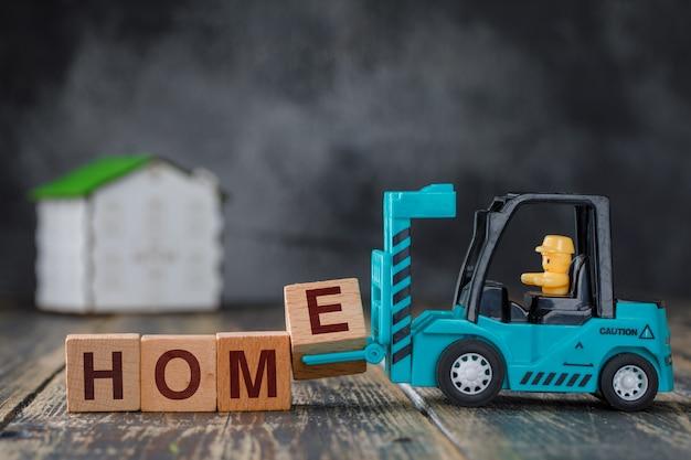 Concept immobilier avec maison modèle sur vue de côté de table en bois. chariot élévateur transportant le bloc de lettre e à l'inscription à la maison.