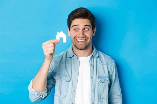 Concept immobilier. mec excité regardant le modèle de petite maison et souriant, louant un appartement, debout sur fond bleu.