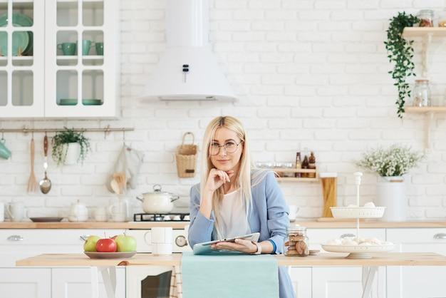 Concept indépendant. belle femme d'affaires dans des vêtements décontractés et des lunettes examine des documents et souriant tout en travaillant avec un ordinateur portable dans la cuisine