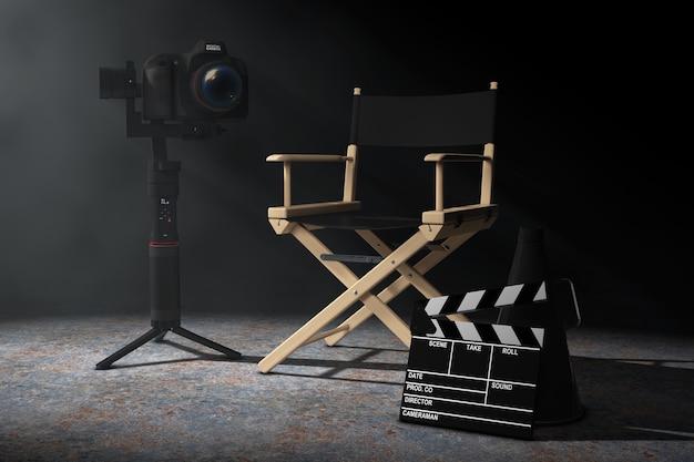 Concept de l'industrie du cinéma. dslr ou système de trépied de stabilisation de cardan de caméra vidéo près de la chaise du directeur, du clapet de cinéma et du mégaphone dans la lumière volumétrique sur fond noir. rendu 3d
