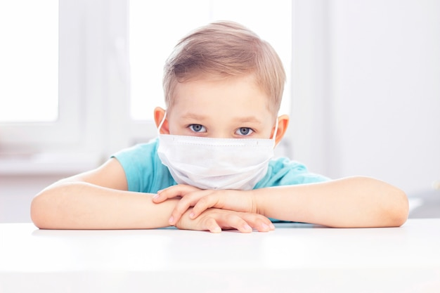 Concept d'infection à coronavirus. garçon dans un masque médical est assis sur une chaise à l'intérieur. garçon ennuyé et triste
