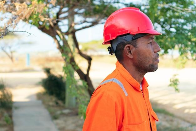 Concept d'ingénieur ou de technicien. homme mécanique en uniforme orange regardant au loin