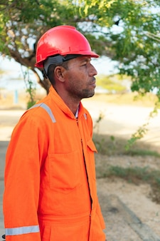 Concept d'ingénieur ou de technicien. mécanicien africain en uniforme orange regardant au loin.