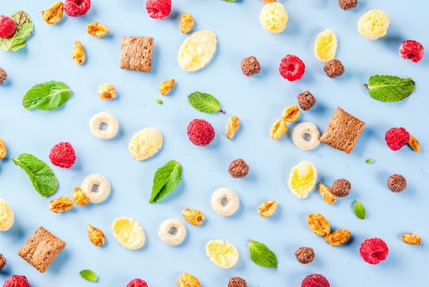 Concept d'ingrédients de petit déjeuner sain. divers petit déjeuner céréales, framboises et menthe sur fond bleu, copie espace vue de dessus