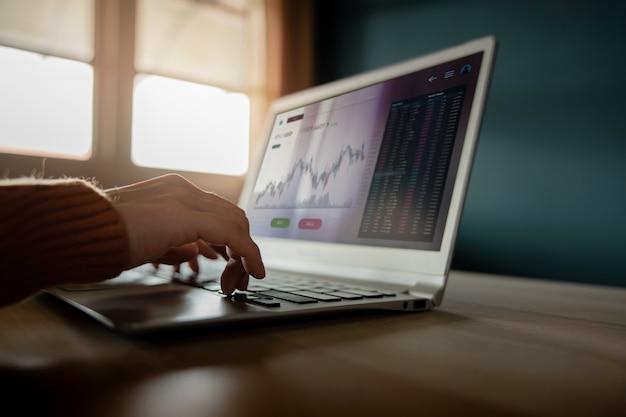 Concept d'investissement en crypto-monnaie personne utilisant un ordinateur portable à la maison pour acheter et vendre des bitcoins