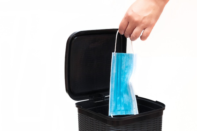 Concept isolé de personne jetant un masque à la poubelle