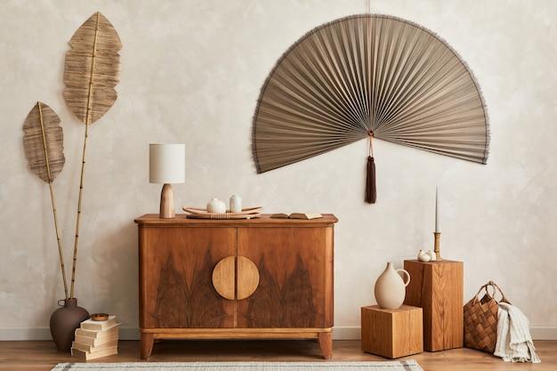 Concept japandi d'intérieur de salon avec commode en bois design, lampe de table, feuille tropicale séchée dans un vase, cubes, décoration, ventilateur japonais et accessoires personnels élégants dans la décoration intérieure.