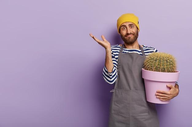 Concept de jardinage et d'agriculture paysagiste. les gestes du fleuriste masculin incertain avec doute