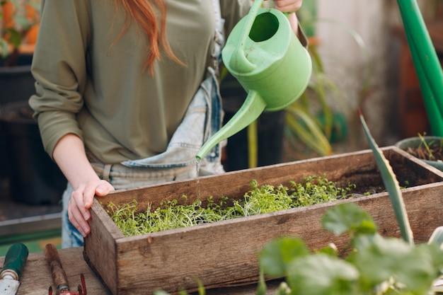 Concept de jardinage à domicile. jeune femme agronome avec arrosoir planter des plantes. plante de jardin maison de printemps.