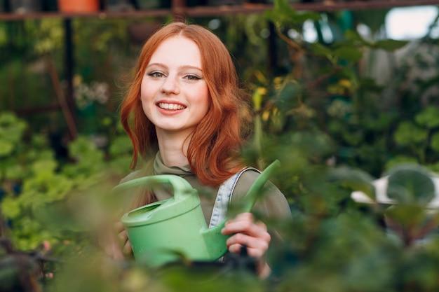Concept de jardinage à domicile. jeune jolie femme avec arrosoir planter des plantes. jardin de maison de printemps.