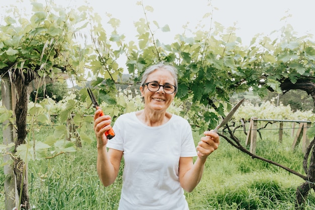 Concept de jardinage et de personnes - femme âgée heureuse plantant des fleurs au jardin d'été
