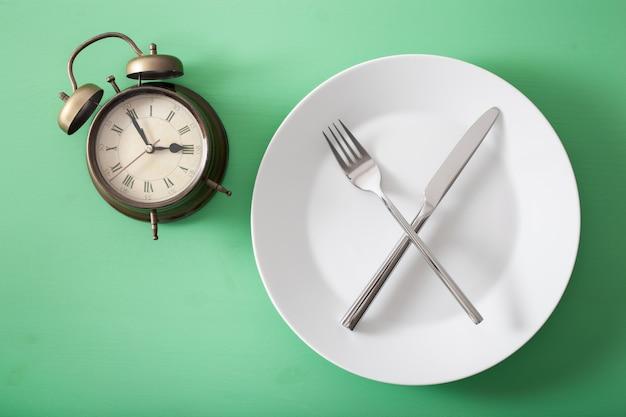 Concept de jeûne intermittent, régime cétogène, perte de poids. fourchette et couteau croisés sur une plaque et un réveil