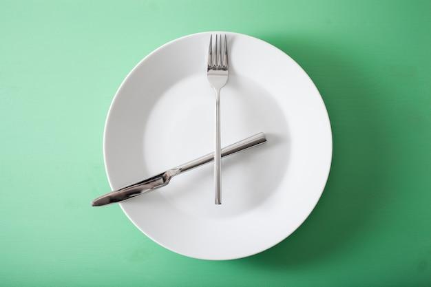 Concept de jeûne intermittent et régime cétogène, perte de poids. fourchette et couteau croisés sur une plaque