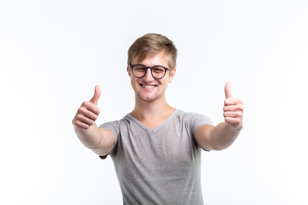 Concept de jeunesse, d'étudiant et de personnes. le jeune homme ressemble à un nerd montre-nous les pouces vers le haut