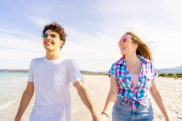 Concept de jeunesse insouciante jeune très heureux gen z vrai couple main dans la main marchant sur le bord de mer