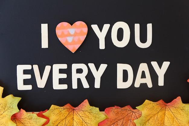 Concept de jour d'amour. le texte en bois reste à la saint-valentin avec une feuille d'érable et une surface noire