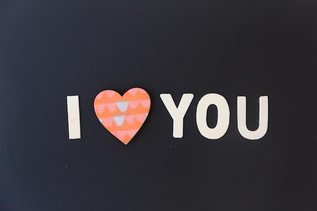 Concept de jour d'amour. le texte en bois reste à la saint-valentin avec un fond noir. saint-valentin, 14 février