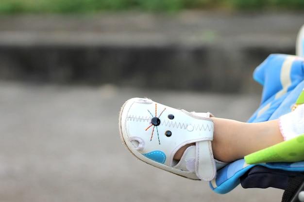 Concept de jour de femme, parties du corps du concept de bébé, une fille d'enfant bébé portant les chaussures blanches. elle est assise dans la poussette.