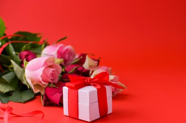 Concept de la journée de la femme et carte de voeux de la saint-valentin. composition avec cadeau, roses. espace pour le texte.