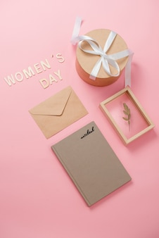 Concept de la journée de la femme, journée de la femme heureuse, journée internationale de la femme. texte de la journée de la femme en bois, cadeau rose avec cadre photo sur fond corail
