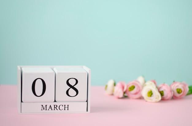 Concept de la journée internationale de la femme. cubes en bois blancs avec 8 mars et fleurs sur fond pastel.