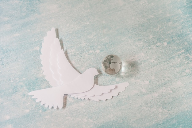 Concept de la journée internationale de la paix: colombe blanche volant au pastel avec globe en verre.