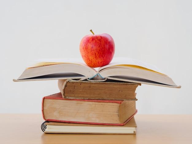 Concept de la journée mondiale du livre. pomme rouge et stylo mis sur une pile de vieux livres