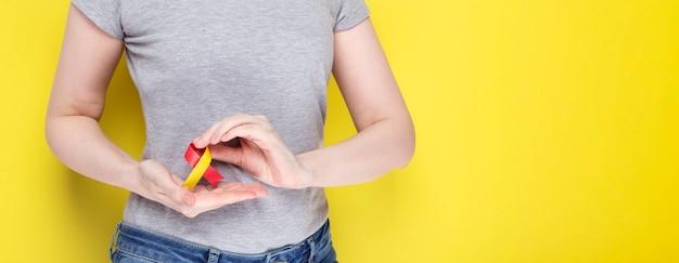 Concept de la journée mondiale de l'hépatite. fille en t-shirt gris tenant le symbole de la zone de ruban rouge-jaune de la conscience.