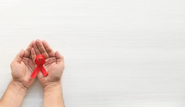 Concept journée mondiale de lutte contre le sida mains d'homme tenant un ruban rouge sur fond blanc transfusion sanguine