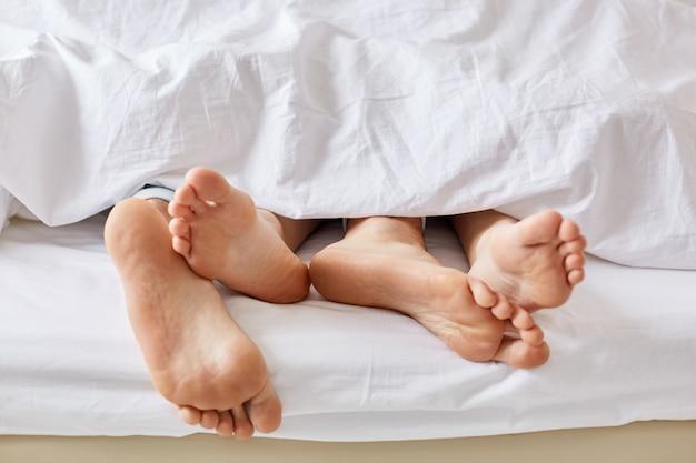 Concept de journée paresseuse. les épouses et les maris nus pieds nus d'une couverture blanche.