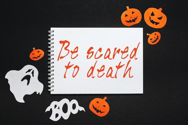 Concept de joyeuses fêtes d'halloween. bloc-notes avec texte soyez mort de peur sur fond noir avec des chauves-souris, des citrouilles et des fantômes