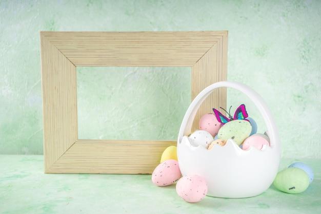 Concept de joyeuses pâques avec des oeufs de pâques dans le panier et des fleurs de printemps. fond de pâques avec espace copie et cadre photo
