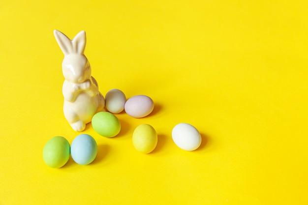 Concept de joyeuses pâques. préparation pour les vacances. bonbons de pâques bonbons oeufs au chocolat et jouet lapin isolé sur jaune branché. espace de copie de minimalisme simple.
