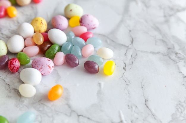 Concept de joyeuses pâques. préparation pour les vacances. oeufs en chocolat de bonbons de pâques et bonbons à la gelée sur fond de marbre gris branché. espace de copie vue de dessus plat minimalisme simple.