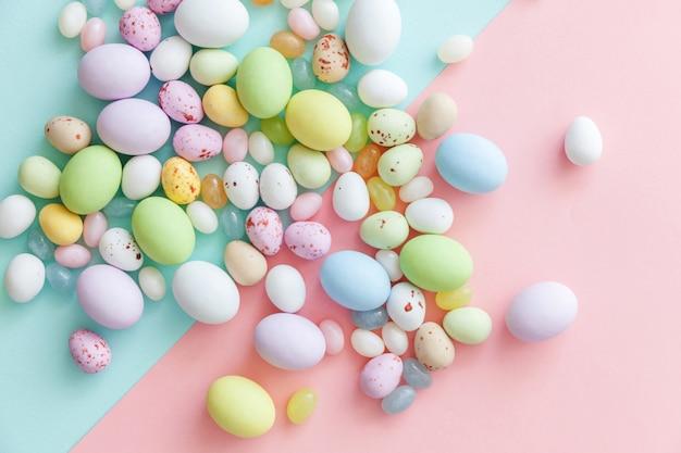 Concept de joyeuses pâques. préparation pour les vacances. oeufs en chocolat de bonbons de pâques et bonbons à la gelée isolés sur rose pastel bleu tendance. espace de copie vue de dessus plat minimalisme simple.