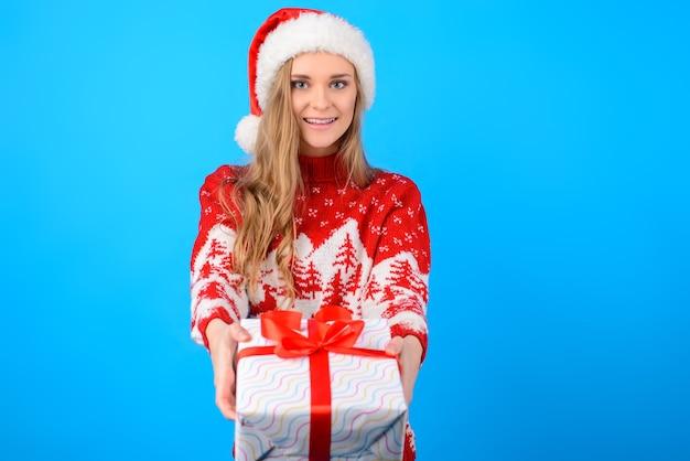 Concept de joyeux noël et bonne année! jolie jolie belle femme charmante en pull tricoté donne un cadeau, isolé sur fond bleu clair