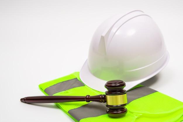 Un concept juridique lié au travail avec des chapeaux de sécurité, des vêtements de travail et un marteau de juge sur fond blanc.