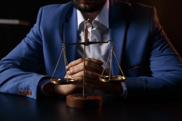 Concept de justice et de droit. avocat de sexe masculin au bureau avec échelle en laiton sur table en bois, reflété