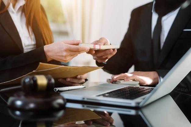 Concept de justice et de droit. transmettre de l'argent de pot-de-vin dans l'enveloppe au bureau de l'avocat.