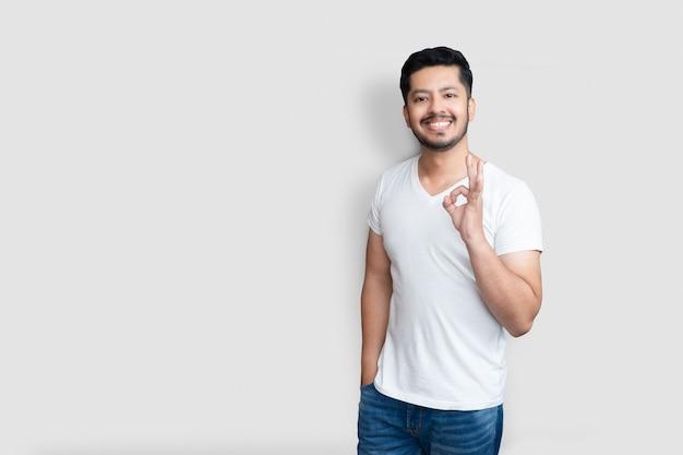 Concept de langage corporel. beau mec asiatique créatif avec barbe légère, levant la main dans un geste correct et souriant tout en aimant le plan fond blanc isolé