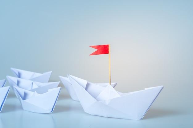 Concept de leadership à l'aide de papier livré avec drapeau rouge sur fond bleu