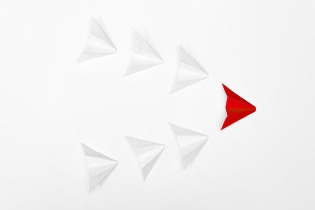 Concept de leadership. avion en papier rouge menant les blancs